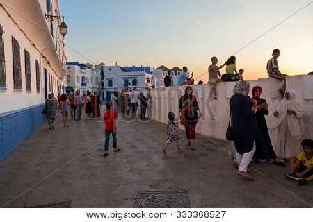 Asilah, Morocco-September 10, 2019: Tourists visiting the rampart in the medina of Asilah at twilight, Morocco