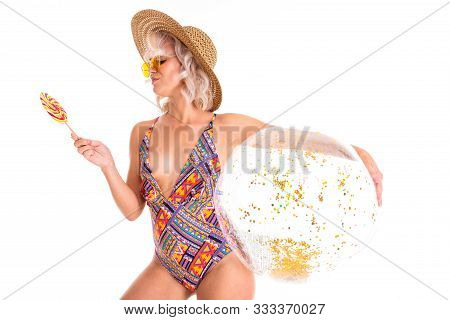 Pretty Blonde Caucasian Female Stands In Swimsuit With Big Rubber Beach Transpatent Ball, Lolipop An