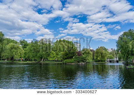 White Dramatic Clouds Over The Lake In Boston Public Garden In Summer Time