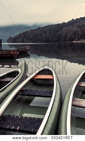 Canoes On Lakeshore In Cold Foggy Autumn Morning In Ribcev Laz, Slovenia