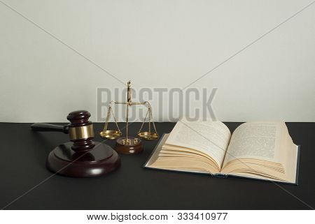 Law Concept. Wooden Judge Gavel, Scales Of Justice And Open Book On Table In A Courtroom Or Enforcem