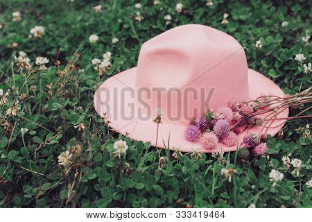 Pink Felt Hat On A Flower Lawn. Vacation, Spring Mood, Summer Fashion, Style Travel.