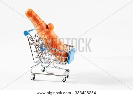 Trendy Ugly Food Concept. Funny Carrot In Toy Grocery Cart On White Background. Vegetable With A Str