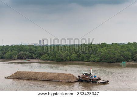 Ho Chi Minh City, Vietnam - March 12, 2019: Song Sai Gon River. Short Tugboat Pushes Long Barge Fill
