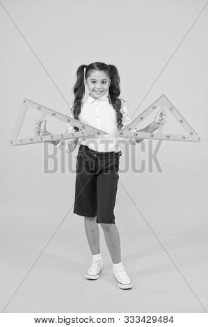 Geometry And Measure. Cute Schoolgirl Holding Triangles For Geometry Lesson On Yellow Background. Sm
