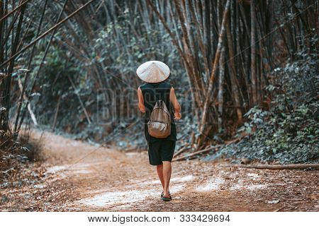 Handsome Man Tourist In Vietnamese Hat Walking At Bamboo Forest