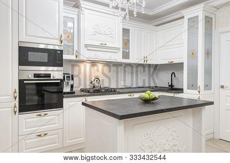 White spacious luxury modern kitchen with island interior