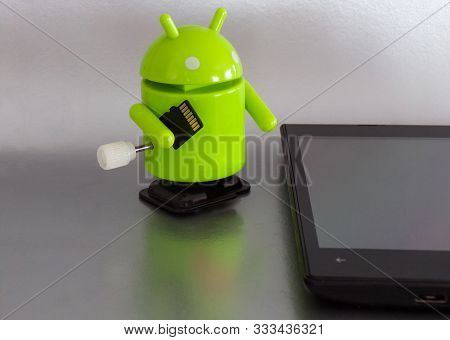 Android Figurine Isolated On White Background. Android With Microsd Flash Drive. Update The Android
