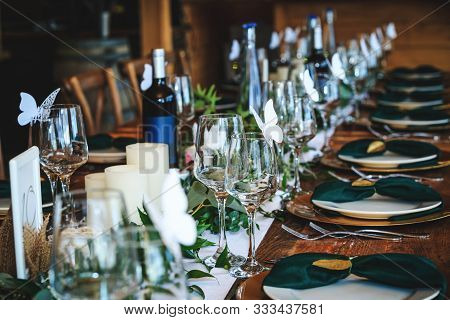 Wine Glasses, Plates, Forks And Green Briefcases For The Banquet. Rustic Wedding Table Setting In Fa