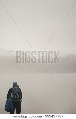 Fogy Mountain Hills And Active Hiker With Backpack In Foreground, Looking Away From Camera