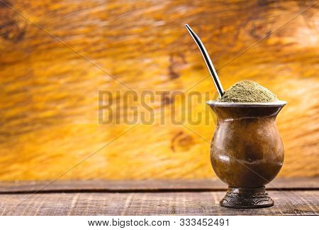 Yerba Mate Tea In Wooden Bowl On Wooden Table. Traditional Drink From Brazil, Argentina, Paraguay An