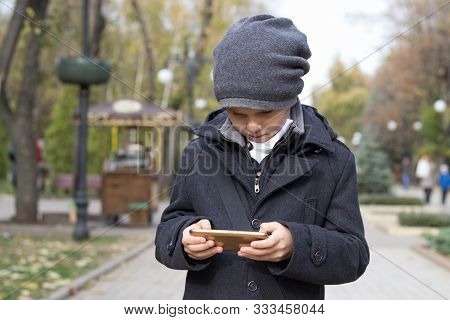 An Elementary School Student Enthusiastically Plays Games On His Smartphone, Holding It In Both Hand