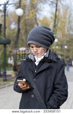 Schoolboy In Hat Holding Smartphone In Hand And Dialing Number On Touch Screen. Outdoors In Park. Da