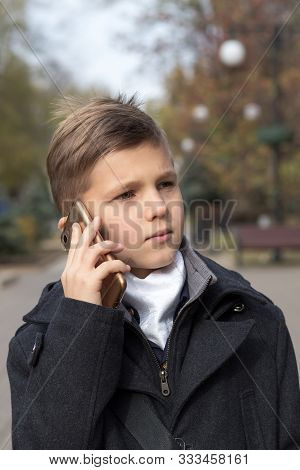 Portrait Of A Schoolboy Dressed In A Business Suit Talking On A Cell Phone, Holding It In His Hand N