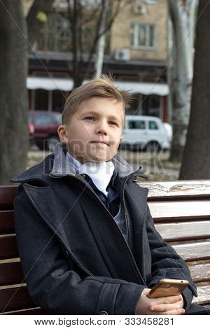 A Boy Sits On A Bench In A Park In Business Clothes With An Appraising Look And A Slight Smile. Thou