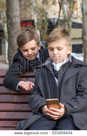 Children Watch An Interesting Video On A Smartphone And Smile While Sitting On A Bench In The Park O