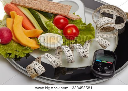 Still life with healthy food, scales, measuring tape and blood glucose meter on white background. Concept: control of level glucose. Healthy lifestyle, healthy food, slimming