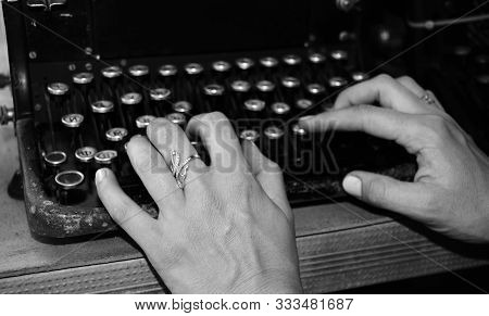 Woman's Hands Writing On A Vintage Typewriter. Hands Writing On Old Typewriter Black And White Photo