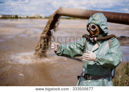 A Male Environmentalist In A Protective Suit And Gas Mask Takes A Sample Of Water. Scientist Doing T