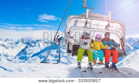 Happy family on ski lift chair enjoying winter ski vacations in mountains  Playing with snow and sun in high mountains. Winter holidays.