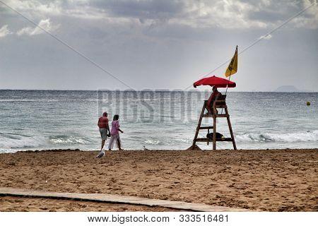Benidorm, Alicante- September 9, 2019: Beach Watcher Under Red Umbrella On Wooden Watchtower On The