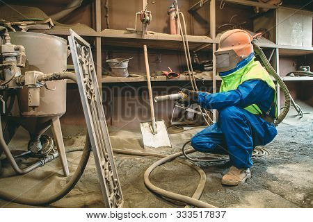 An Employee Prepares A Metal Part For Painting. A Harsh Man Works In The Factory. Sandblast. Blast I