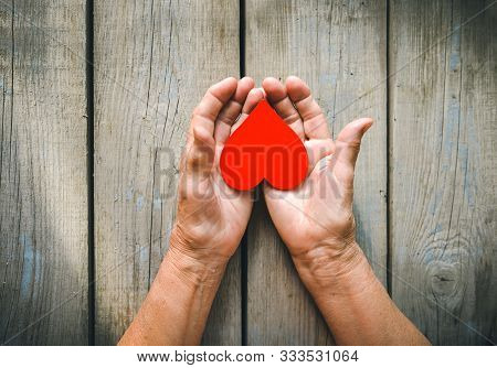 Elderly Woman Hands Closeup Holding Red Heart. Rustic Wooden Table Background. Love, Warmth, Take Ca