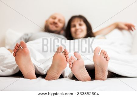 Love, dating, romantic mood, happy people and bedtime concept - attractive caucasian couple in relationship lying and hugging on bed in bedroom