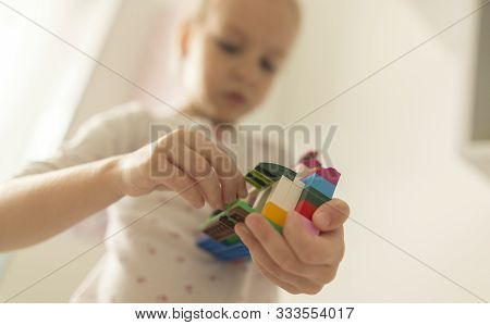 Cute Funny Preschooler Little Girl Playing With Construction Toy Blocks Building And Tower In A Sunn