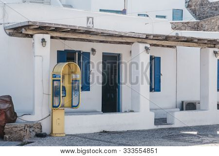 Mykonos Town, Greece - September 23, 2019: Yellow Public Telephone On A Street In Hora, Also Known A