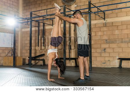 Full Length Of Young Man Assisting Friend In Doing Handstand At Gym
