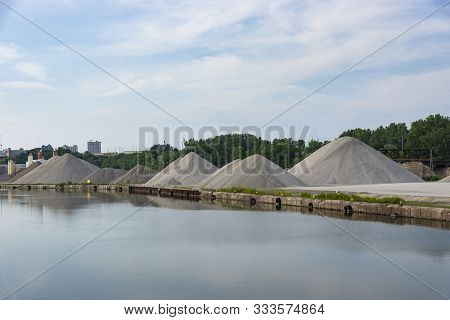 Mounds Of Assorted Aggregate Materials Stored Along The Bank Of The Cuyahoga River In Cleveland, Ohi