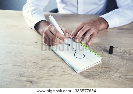 Man Hand Question Mark On Notepad On Desk