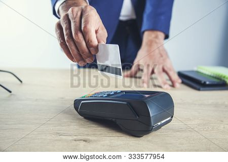 Man Hand Credit Card With Terminal On Deak