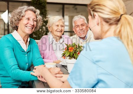 Caregiver takes care of a group of happy seniors in the retirement home