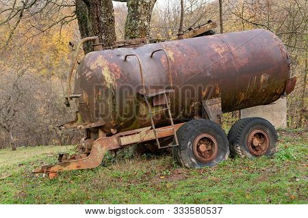 Rusty Tanker. Old Rusty Tank Truck With Pump Mechanism. Old Abandoned Machinery.