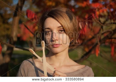 Young Girl With Short Blond Hair Is Holding A Bamboo Toothbrushes Outdoors During Sunny Weather In A