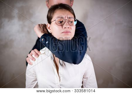 A Man Stands Behind The Girl And Makes Her A Choking Grip. The Girl Cannot Resist And Just Bitterly