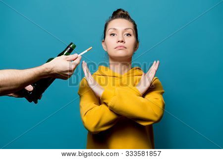 Girl In A Yellow Sweatshirt Refuses Alcohol And Cigarettes, Preferring A Healthy Lifestyle