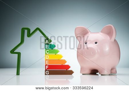 Green House Energy Efficiency Graph Near The Pink Piggybank On White Desk Against Blue Background