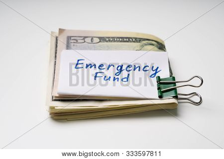 Black Paper Clip With Folded Fifty Dollar Banknote And Emergency Fund Text On Paper