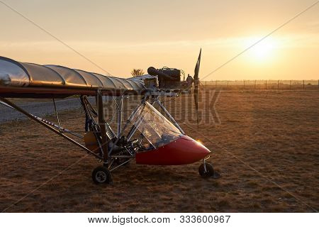 Ultralight Single-engine Single-seat Aircraft Stands On The Airfield In The Early Morning.