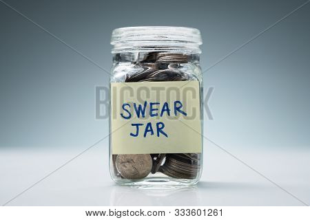 Close-up Of A Glass Jar With Swear Jar Text Filled With Coins Against Grey Background