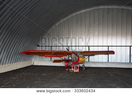 Very Small Single-place Ultralight Glider Stands In The Corner Of A Metal Hangar.