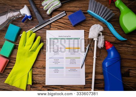 Close-up Of Various Cleaning Products Around Weekly Cleaning Plan Form With Pen
