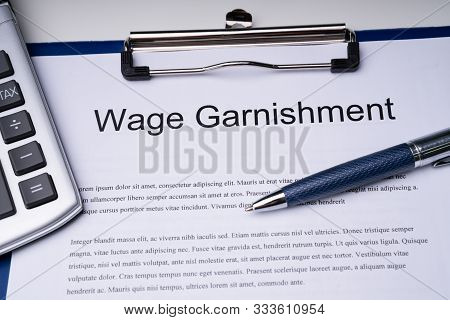High Angle View Of Wage Garnishment Documents With Calculator And Pen Over Clipboard