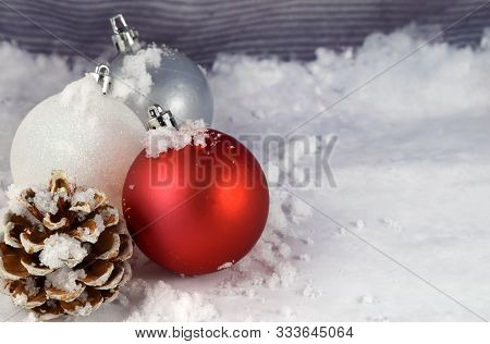 Several Festive Christmas Ornaments And A Pinecone Grace This Wintery Background. Features Plenty Of