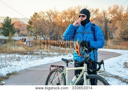 Senior male cyclist is putting a balaclava and helmet on for cold winter biking, city of Fort Collins in northern Colorado has a dense network of recreational and commuting multi use trails