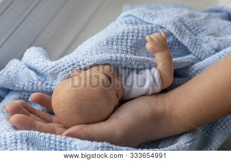 Premature Newborn Baby Wrapped In Blue Blanket With Mothers  Arm And Hand Represented By A Reborn Do