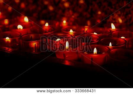 Red Wax Candles Burning Brightly In The Black Background/ Conceptual Image Of Light And Hope